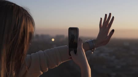 raios de sol : Long haired young woman standing from the back uses mobile phone at city blurred background with sunset or sunrise. Enjoying the time, making photo of her hand in front the sun rays while standing on the roof Stock Footage