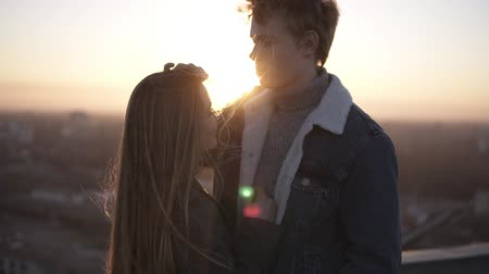 愛撫 : Young blondy boy and her long haired girlfriend are standing on the roog during the sunrise embracing. Enjoying the togetherness, caressing each other and looking on horizon on cityspace