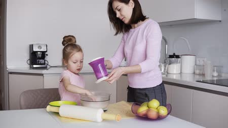 koca : Little cutie daughter is helping her mother on the kitchen, add flour with sifter and mixing the ingredients in bowl. Brunette woman helping to manage. Sow motion Stock mozgókép
