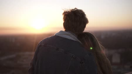 pažba : Close up of young long haired woman and man looking at the city at sunset standing on the roof of the high building. Watching the sunset embracing. Backside view Dostupné videozáznamy