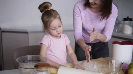 asistan : Cheerful mother with her child, a girl having fun while preparing a cake in their modern, white kitchen. They play clapping hands with flour Stok Video
