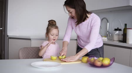 разделочная доска : Mom and daughters cooking healthy food at home and having fun. Young woman cutting yellow apple on the desk in front her daughter. Household, teamwork helping, maternity concept