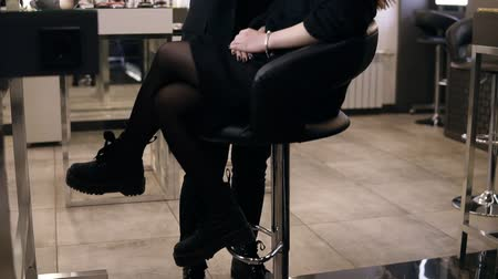toner : Brunette woman in black suit with pony tail applying cosmetic s on models face with a large black make up brush. Girl in black clothes in the salon doing make-up, apply powder on the skin, foundation or toner. Bright light bulbs. Footage from down below Stock Footage
