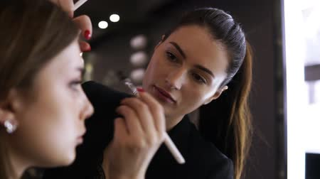 kaşları : Attractive young make up model with natural makeup is sitting in front the mirror. Visagist works from the side, applying the eyeshadows on her eyelid. Close up view