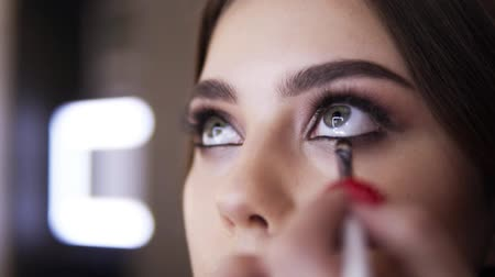 マスター : Close-up of make-up artist hand with a small brush works through the lower eyelid, makes smoky eye makeup. Beautiful scene of young womans eyes with long lashes.Visagist makes evening makeup for an ev