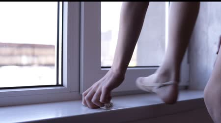 тапочка : Unrecognizable ittle girl engaged in gymnastics puts on her ballet shoes by the window in a modern specious studio. Go into sport, active lifestyle. Rhythmic gymnastics for girls