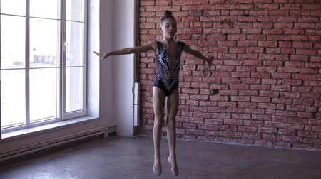 fegyelem : Artistic young girl engaged in rhythmic gymnastics in artistic bodysuit standing near the windows and preparing for jump. Young gymnast training in the gymnastics school or studio. Slow motion