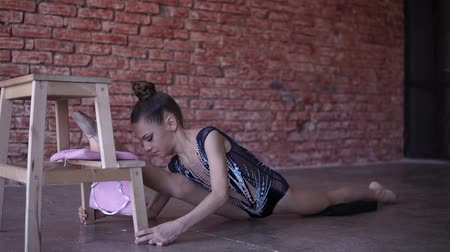 banquinho : Flexible teenage girl warming up stretching in a studio in front the brick wall. Leg split leans fore leg on a wooden stool. A girl in a performance suit does stretching - bending forward and backward with the body