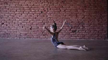 колено : Beautiful fit gymnast girl doing gymnastic exercises in brick design studio - doing splits, coups on the floor. Slow motion