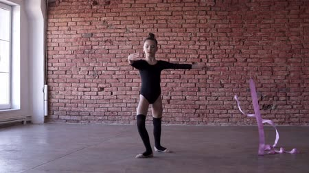 ritmische gymnastiek : Portrait of little girl in black bodysuit engaged in gymnastics spinning with pink ribbon in front of camera in the studio with the red brick wall background. Slow motion