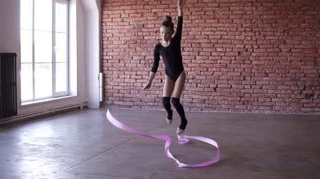 ритмичный : Rhythmic gymnastics for girls. Cute girl exercising in dancing stuido alone.Dancing, spinning with pink ribbon. Slow motion footage. Brick wall on the background Стоковые видеозаписи