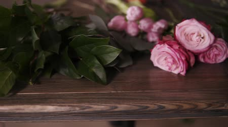 florista : Close up footage of flowers, ribbons and other tools of professional florist lying on table. Arrangement and packaging of the bouquet. The concept of flower delivery, workshop or online store Stock Footage