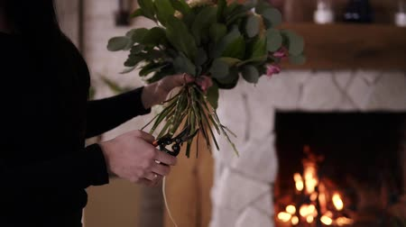 preciso : Professional florist cuts the stems of flowers in the bouquet. Woman in black assembles a perfect bouquet. Final touches: you need to cut the stems before bouquet is ready. Firelace on the background