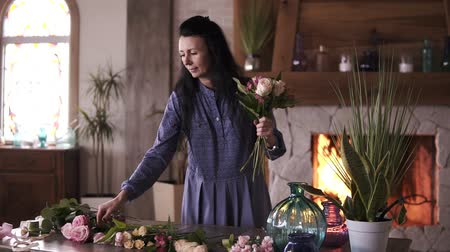 projetado : Longhaired female florist in blue dress holding a half made bouquet and adding flowers and plants to composition. Designing, floral workshop, leisure. Blurred picture of fireplace on the background