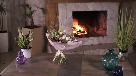 kwiaciarnia : Beautiful bouquet of pastel colors flowers in pink decorative paper stands on the stems on a gray table after the flower masterclass. Flowers decoration design concept. Fireplace on the background. Stedicam. Slow motion