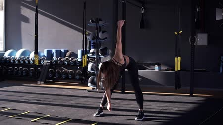 только один человек : Beautiful young slim woman athlete in a black sportsuit makes the slopes - warm up before training. Front view of a girl stretching in the gym Стоковые видеозаписи