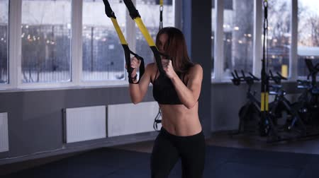 süspansiyon : Muscular, fitness girl in black sportswear doing legs exercises while holding weight straps. Squatting, bonding legs, lift high the knees. Grey coloured, modern gym. Slow motion Stok Video