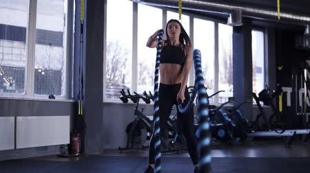 stanovena : Front footage of determined middle-aged woman battling ropes in gym during cross-training workout. Slow motion