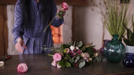 florista : Adult florist master arranging the big assortment flowers and plants on the counter for the future composition. Workshop, designing flowers, handcraft concept. Fireplace on the background Stock Footage