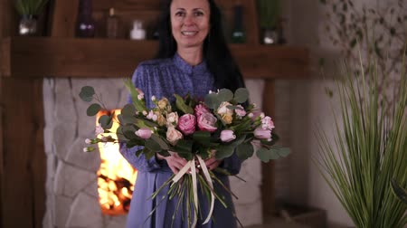 самодельный : Professional woman floral artist, florist in blue dress perfoms the selfmade beautiful bouquet of different roses and leaves at workshop, flower shop or home studio. Floristry, handmade and small business concept