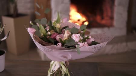 organizing : Beautiful bouquet of pastel colors flowers in pink decorative paper stands on the stems on a gray table after the flower masterclass. Flowers decoration design concept. Fireplace on the background