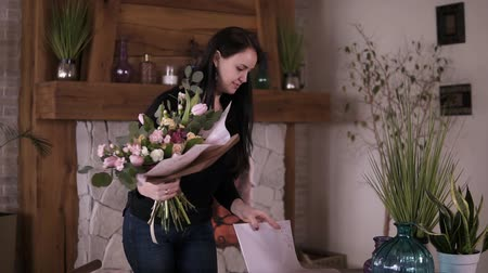 dekoratör : Brunette woman in casual floral artist, florist wraps flowers - pink roses in gift paper at workshop, home studio. Floristry, handmade and small business concept. Slow motion Stok Video