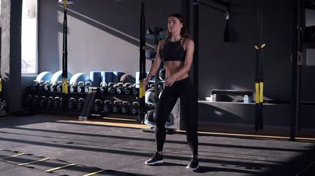 lift ups : Full length of professional sportswoman in black sportwear doing exercise for butt muscles and legs. Attractive girl is practicing deep sit ups in modern gym