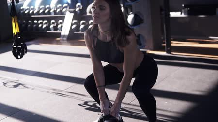 şartlar : Long haired young fit woman clapping hands with magnesium on them before lifting weights, kettlebell 10 kilos. Modern gym, sunlight from the window on the background