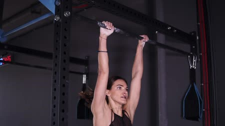 mento : Side view of muscular adult sportswoman in black leggings and bra hanging on metal bar in gym and determinated doing chin-ups