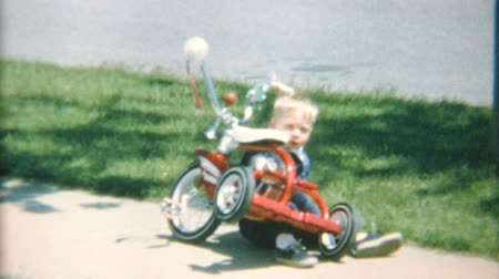 pré escolar : A cute little boy crashes his tricycle on the sidewalk in the summer of 1967.