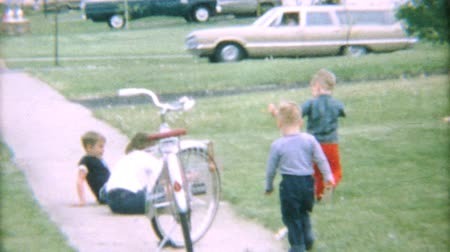 pré escolar : Two little boys running and playing outside on the sidewalk during the summer of 1967.