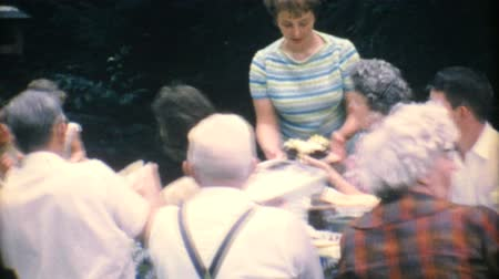 домохозяйка : A mom serves delicious birthday cake to her family at the big summer reunion in 1967.