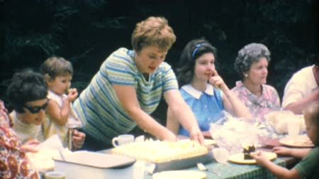 домохозяйка : A mom cuts delicious birthday cake for her family at the big summer reunion in 1967. Стоковые видеозаписи