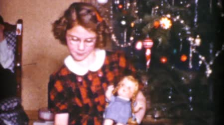 долл : A cute little girl plays with her new doll that she got from her parents on Christmas Day in 1955.