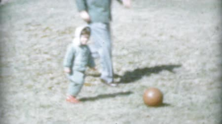 сбор винограда : A cute little girl has fun playing soccer in the backyard with her Daddy in 1959. Стоковые видеозаписи