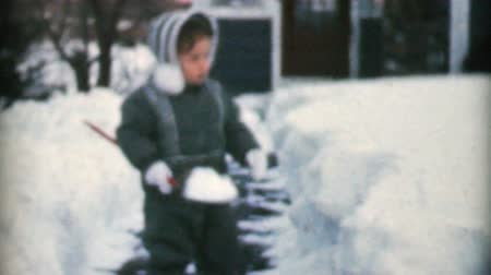 küçük kız : A cute little girl plays outside and helps to shovel the front sidewalk on a snowy winters day in December 1959.