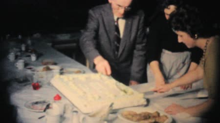 gestão : Office management careful cuts a big slab cake at the year end company Christmas party in 1962. Stock Footage
