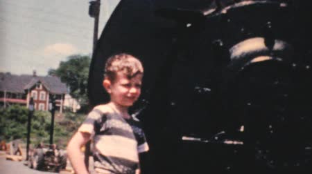 mozdony : A cute little boy stands beside an old steam train locomotive in the fall of 1959. Stock mozgókép