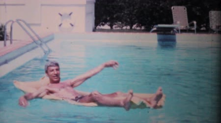 colchão : A man enjoys himself while floating on an air mattress in his pool while on holidays in Florida in 1969.