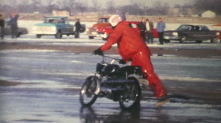motorsports : Men and women race fast motorcycles on a frozen lake in the winter of 1970. Stock Footage