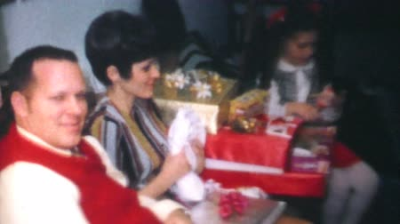 ozdobnik : A family enjoys opening Christmas presents together on Christmas morning in 1970. Wideo