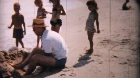 sadece : A man enjoys playing on the beach with some kids in Ocean City, New Jersey while on his honeymoon in 1958. Stok Video