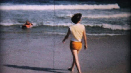 casado : A pretty woman enjoys wading into the ocean on the beach in Ocean City, New Jersey while on her honeymoon in 1958. Stock Footage