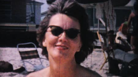 sadece : A pretty woman enjoys sunbathing on the beach in Ocean City, New Jersey while on her honeymoon in 1958. Stok Video