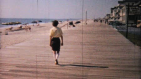 sadece : A pretty woman enjoys walking on the boardwalk near the beach in Ocean City, New Jersey while on her honeymoon in 1958.