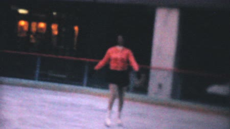 skate : A teenage girl enjoys practicing leaping and jumping while figure skating at the Penn Center ice rink in downtown Philadelphia in December 1962. Stock Footage