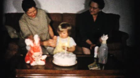 долл : AKRON, OHIO, JUNE 1961: A cute little girl celebrates her first birthday in 1961 by blowing out the candles on her birthday cake in Akron, Ohio. Стоковые видеозаписи