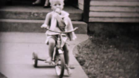 brancos : A cute little boy rides his new tricycle while he sucks his thumb in the summer of 1957.