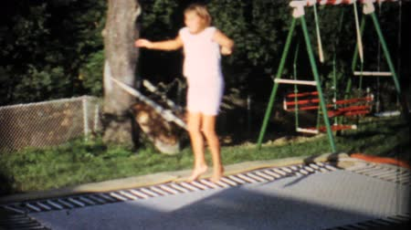 jimnastik : A teenage girl has fun jumping on an in ground trampoline in the back yard in the summer of 1967.