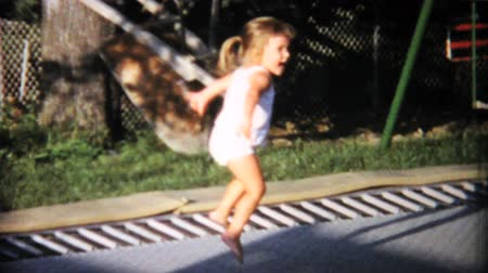 jimnastik : A little girl has fun jumping on an in ground trampoline in the back yard in the summer of 1967.